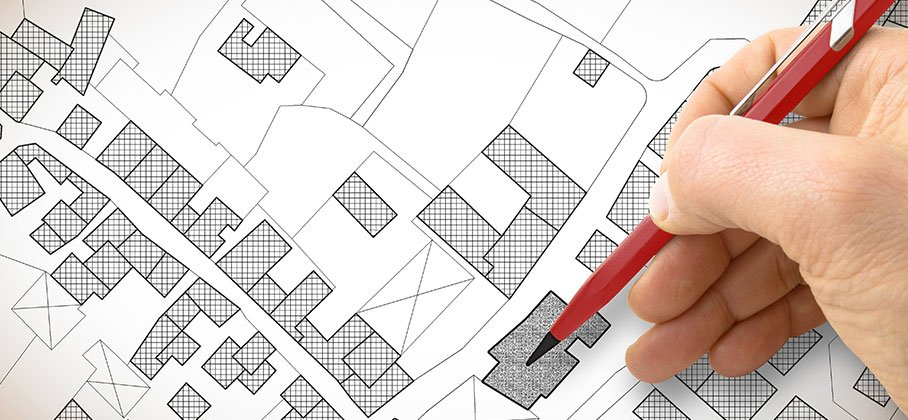 Person with pen pointing to a zoning property map
