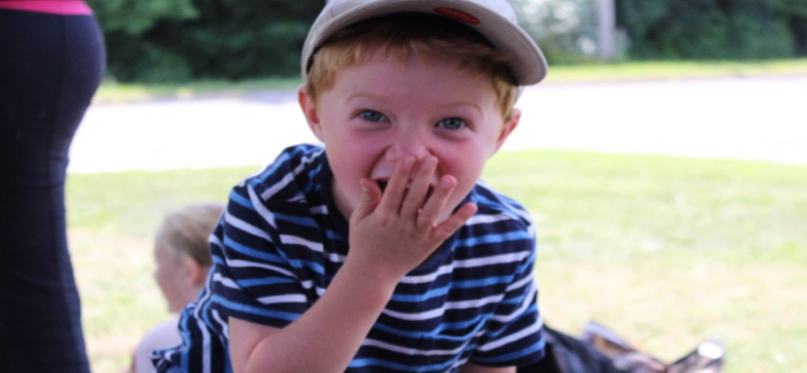 young boy smiling and covering his mouth with one hand as if he is surprised
