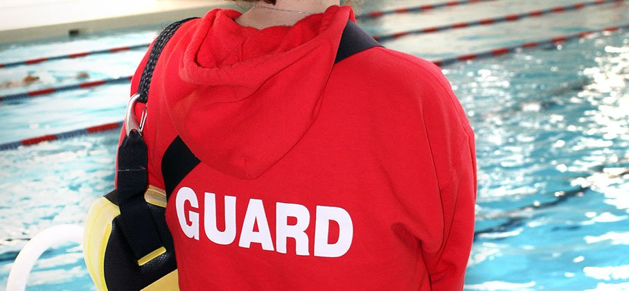 text saying GUARD on the back of a sweater someone is wearing, standing in front of an indoor recreational pool