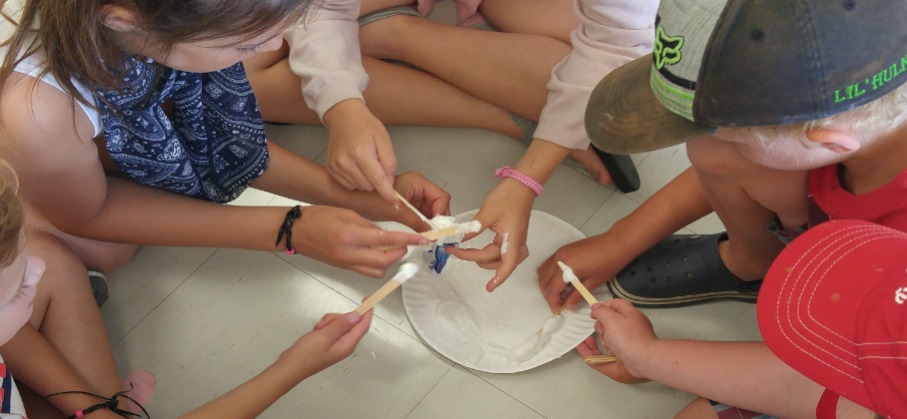 children seated on the floor around a paper plate craft activity