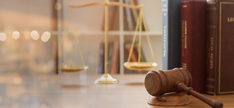A gavel in focus in front of a set of gold scales